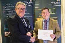 Alex receives the Mercer Scholarship from Roger Mercer