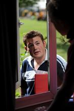 Students having a discussion through an open window in halls