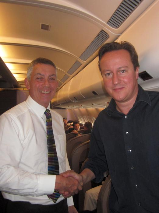 Professor Mills on the plane in Brazil with Prime Minister David Cameron