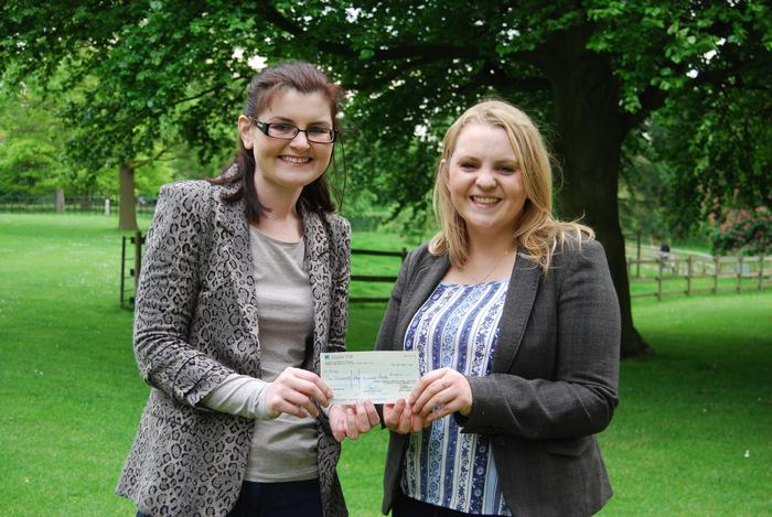 Kate Jones (L) receives the cheque on behalf of R.A.B.I., from student Catherine Bletcher
