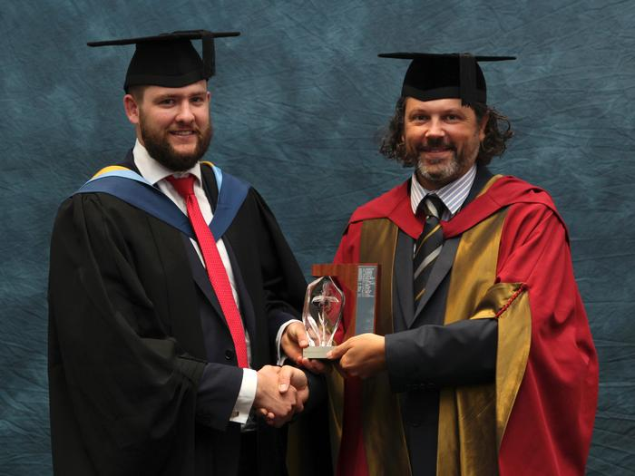 "Jono Thomson BSC (Hons) Agriculture receives the Dr Norman Gill Crop Science Award from Principal Lecturer Dr John Reade. This award is made annually at Harper Adams University graduation for outstanding performance in the areas of plant and crop science.  His tutors wrote: ""Jono Thompson has gained a First Class degree in Agriculture, being consistently excellent across all his modules. Jono is originally from Zimbabwe and came to the UK with an enthusiastic approach to study and life at Harper Adams. He chose to look at agriculture as a broad industry, adding to his general agriculture by doing his placement at Co-op farms, where he was involved with fresh produce.  In his final year project Jono developed a screening protocol for veg breeding - one that we are using in further research.""  Jono, 27, is now working as a farm manager in South Shropshire. He also received the Society of Biology Top Student Award for achieving the highest percentage mark in a bioscience based degree.  Jono receives free membership of the Society of Biology in recognition of his outstanding performance in bioscience aspects of his degree."