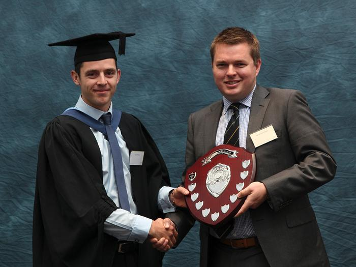 "The Frontier Agriculture Trophy is presented to James Willcox, BSc (Hons) Agri-business, by Robert Preston, Key Account Manager at Frontier Agriculture. This award is made annually at the Harper Adams University graduation prize-giving to the best student on the BSc Agri-Business degree.  James, 22, from Petersfield, Hampshire, achieved a 1st class honours degree. He carried out his year-long work placement with Andersons, an agricultural consultancy business, and wrote a dissertation titled ""Disparity and determinants of cereal farm profitability within the UK""."