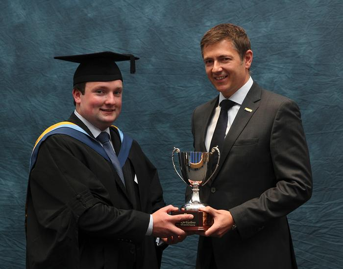 Cormac Flaherty. BEng (Hons) Agricultural Engineering, receives the New Holland Trophy from James Ashworth, General Sales Manager at New Holland Agriculture.