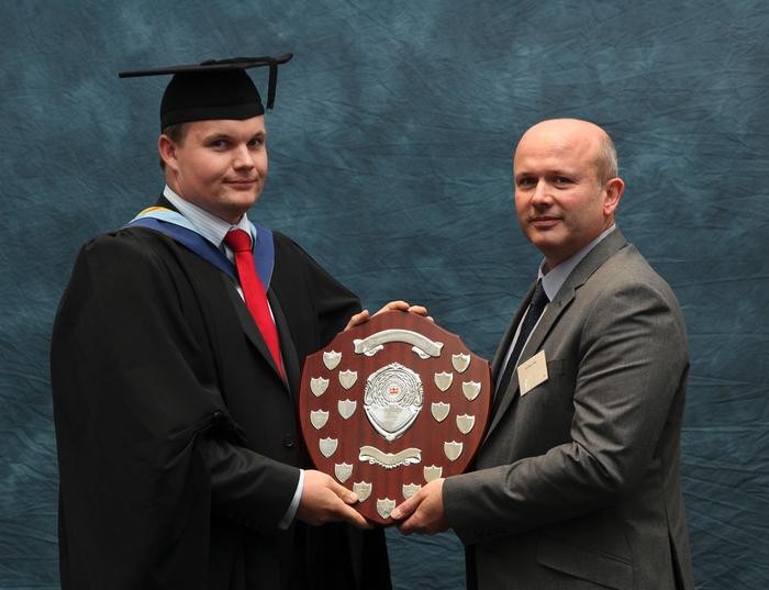 "The Terex Shield is presented to George Cooper, BSc (Hons) Off Road Vehicle Design, by Steve Price. The award is made annually at the Harper Adams University graduation prize-giving to the best student off-road vehicle design student. Lecturer Greg Rowsell said: ""George, a JCB Scholar, graduates today with a first-class honours. He completed his industrial placement year with JCB, who also sponsored his final year project for which he investigated loadall hydraulic performance. George leaves us to start his graduate career with JCB as a Loadall Test & Development Engineer"