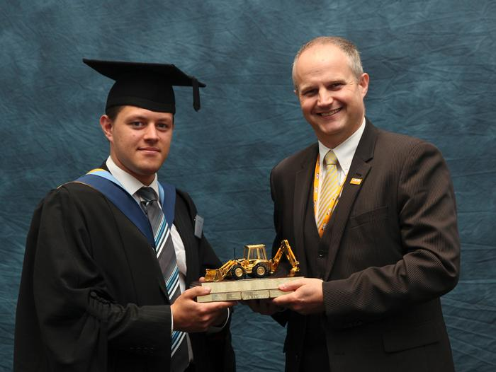 "William Copland, BEng (Hons) Off Road Vehicle Design, receives the JCB Trophy from Simon Wood, Technical Excellence Leader at JCB, at the Harper Adams University graduation prize-giving. Programme manager Greg Rowsell said: ""William graduates with a first-class honours degree, and also as the highest performing student on the BEng Off Road Vehicle Design course"