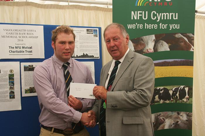 Alex Robinson receives the Gareth Raw Rees Memorial Scholarship by Dai Davies OBE, Chairman of NFU Mutual's Advisory Board for Wales at the Royal Welsh Show.