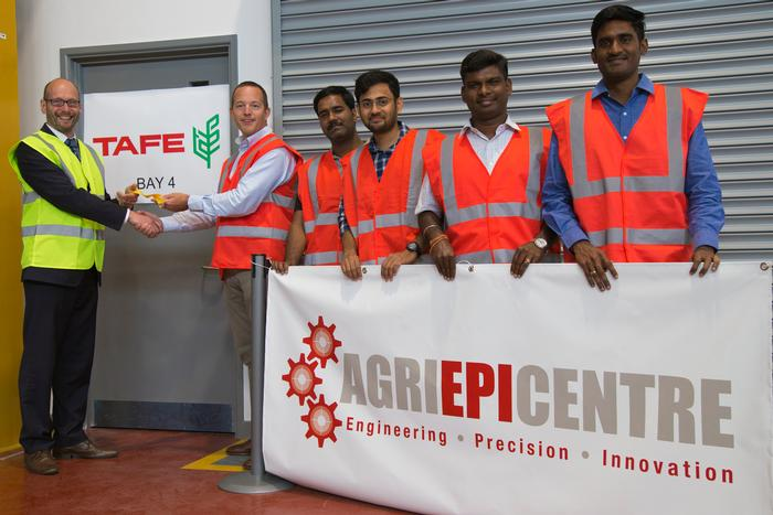 TAFE Chief Technology Officer James Miller receiving the key to the workshop from Agri-EPI Centre Newport Hub Manager Lee Williams, along with the team of engineers from TAFE's Centre of Excellence
