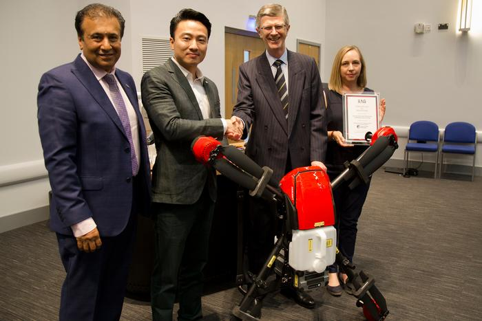 XAG Co-Founder and Vice President Justin Gong, presenting the P20 UAV spray drone to Harper's Parmjit Chima, Dr David Llewellyn and Debbie Heeks.