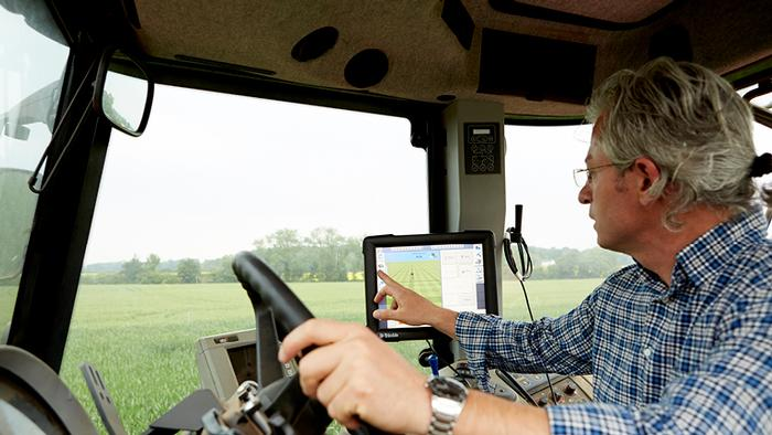 Man in tractor cab operating tablet device