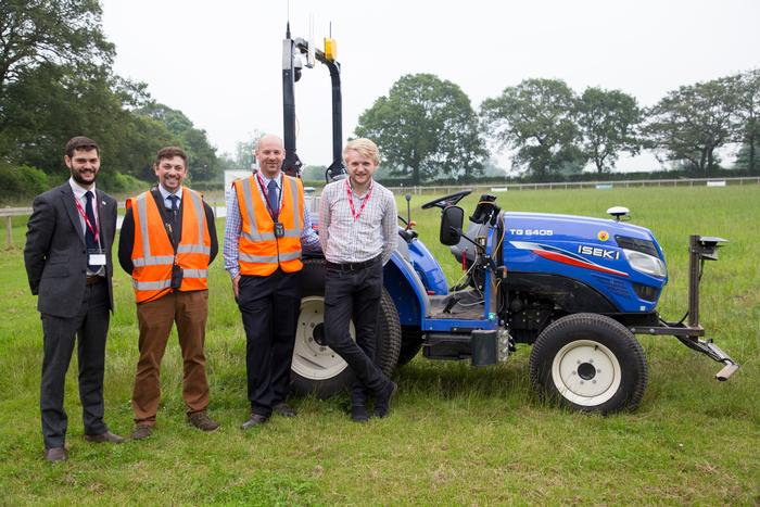 Four engineers standing next to a blue autonomous ISEKI tractor