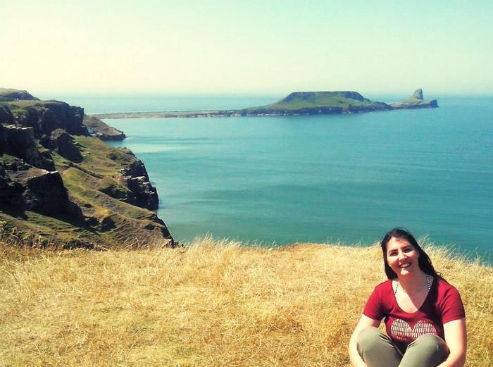 Valeria smiling at camera in front of Worm's Head, Swansea