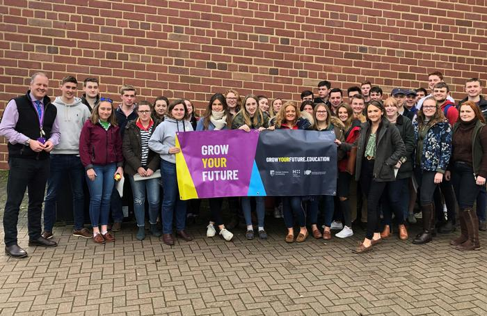 Andrew Black with group of first year students holding sign for 'Grow Your Future'
