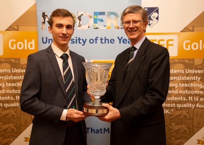 Vice-chancellor presenting student with trophy