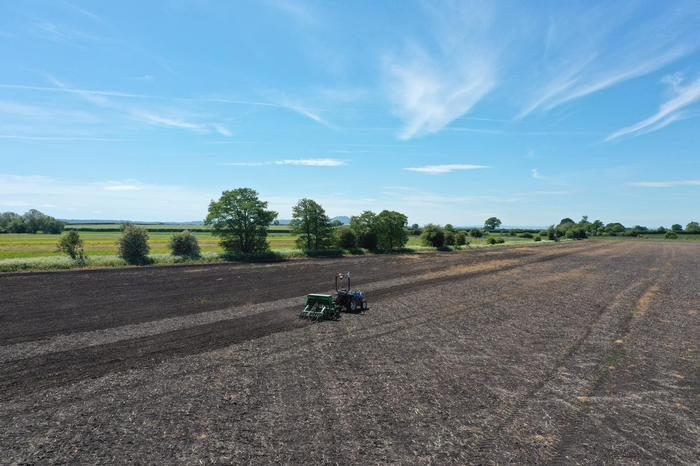 The ISEKI autonomous tractor drilling in an agricultural field with The Wrekin in the background