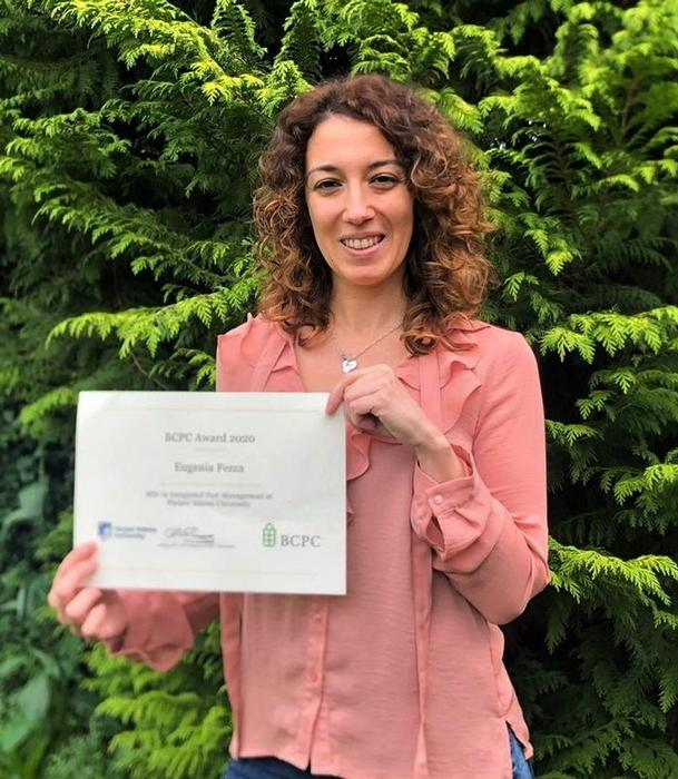 Eugenia holds certificate in pink blouse in front of fir tree