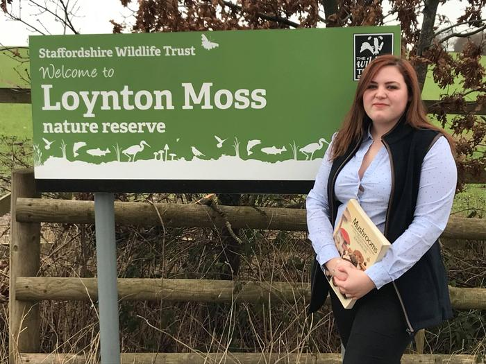 Young woman with brown hair wearing a pale shirt and dark gilet stands by the sign for Loynton Moss, with fields in the background