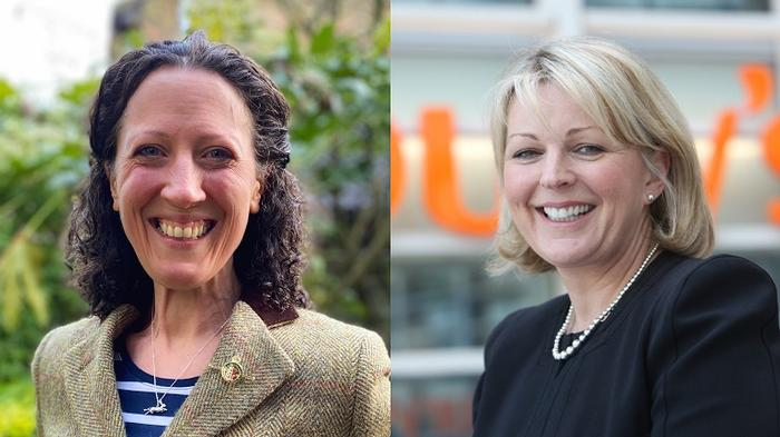 Headshots of two women smiling towards the camera – one in a striped top and jacket in front of greenery and one in a black dress in front of Sainsbury's supermarket branding.