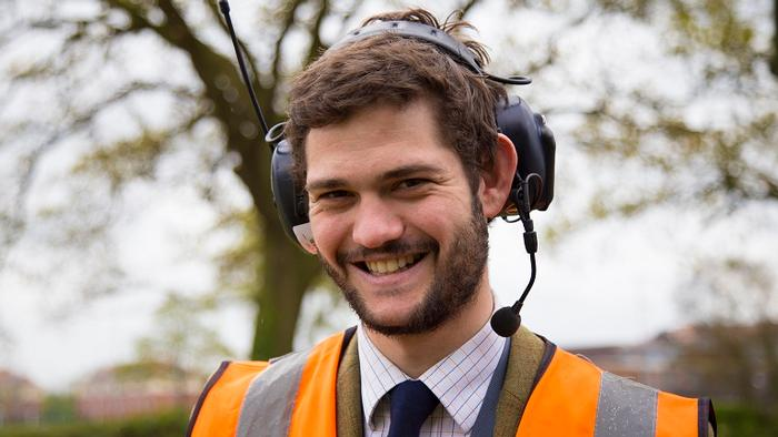 Kit Franklin - a man in a hi-viz jacket and ear protectors smiles at the camera while out in a field.