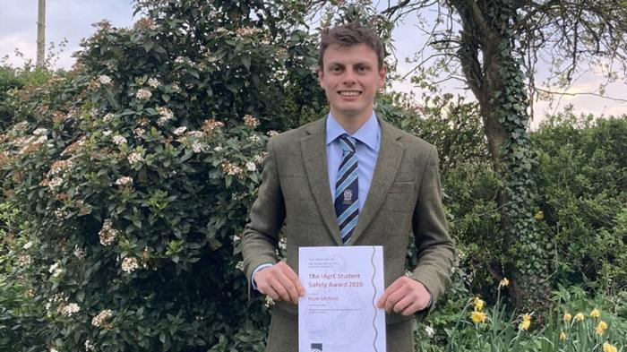 Huw Gilchrist - a man, wearing a suit and tie, stands in a garden holding an IAgrE certificate.