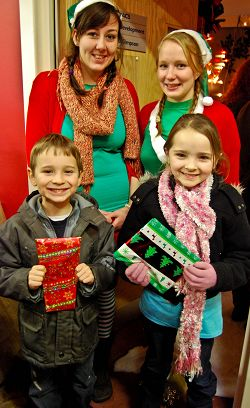 Student elves L-R are Rosie Riches and Efa Jones with Jack Bate, aged six and Leah Bate, aged eight, from Newport