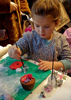Florence Furniss, aged five, has a go at decorating a cup cake