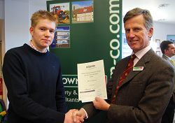 Student Charles Ackerley is pictured receiving the first prize for the Brown & Co Award from David Hooper MA FRICS FAAC, a partner of the firm