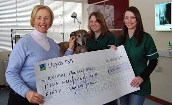 Jo, Beth and Chloe the dog hand over the cheque to Karen Pearson