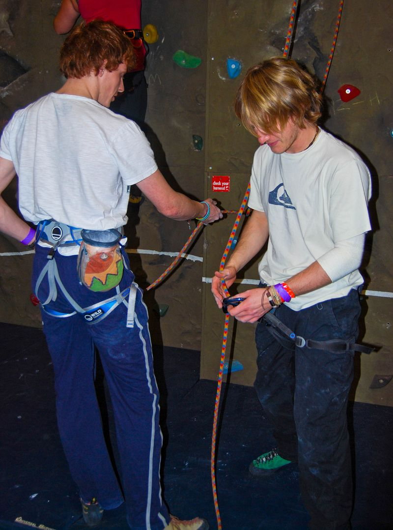 Students help eachother with the climbing ropes